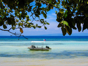 A Dive Boat anchored on a white sand beach in Siquijor