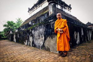 A young Buddhist monk stands in front of a stone temple in Luang Prabang, Laos