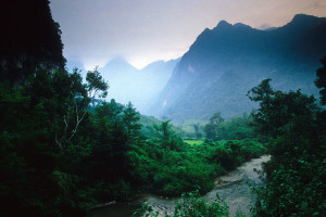 Karst Limestone mountains tower above a small river near Nong Khiew in Laos